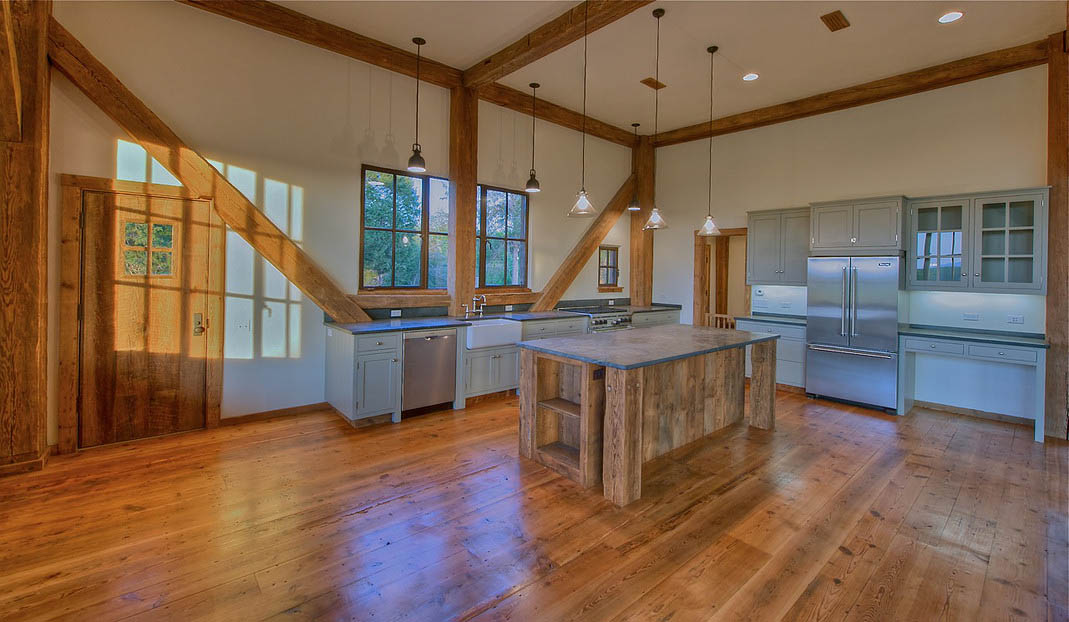 Saine Cabinetry designed this farmhouse kitchen featuring open spaces rustic wood cabinetry.